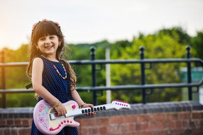 happy kid is playing the guitar - ده دلیل اهمیت بسیار هنر در آموزش و پرورش کودکان